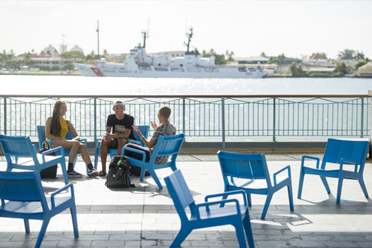3 students chatting on blue chairs near the pier at Aloha Tower. Behind them, a boat is in 日e water.